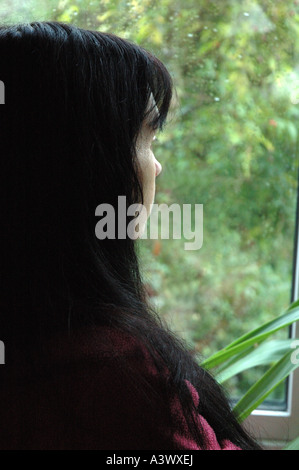 woman staring out of a rain splashed window in winter - Stock Photo