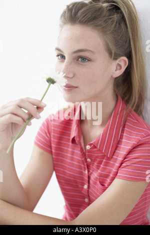 A young woman smelling a flower - Stock Photo