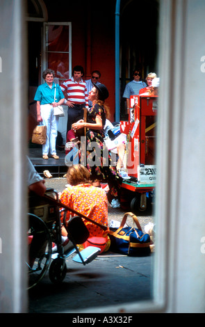 Street musicians and onlookers reflected in window New Orleans Louisiana USA - Stock Photo