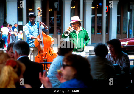 Double bass and trumpet buskers play outside cafe New Orleans Louisiana USA - Stock Photo