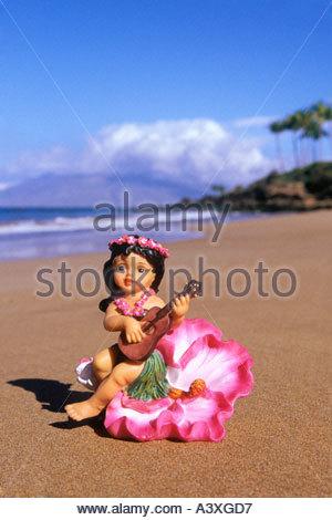 Figurine of Hula dancer with ukelele on beach at Wailea on the island of Maui in the state of Hawaii USA - Stock Photo