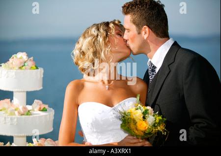 bridal couple outside with weddingcake - Stock Photo