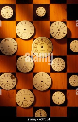 Watch dials on checker board - Stock Photo