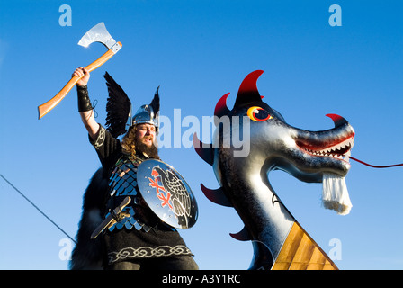 dh Up Helly Aa procession LERWICK SHETLAND Guizer Jarl Einar of Gullberuvik Viking longship galley Moogi prow wave - Stock Photo