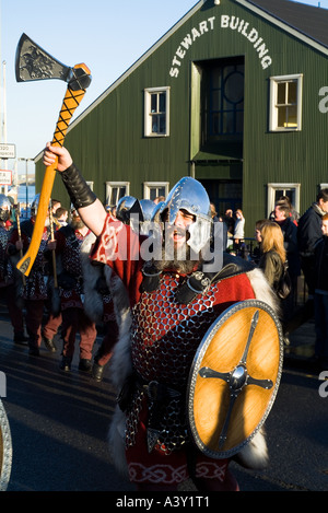 dh Up Helly Aa procession LERWICK SHETLAND Guizer Jarl Einar of Gullberuviks Viking cheering with axe and shield - Stock Photo