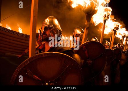 dh Up Helly Aa fire procession LERWICK SHETLAND Vikings escorting Viking longship torch parade festival torches - Stock Photo