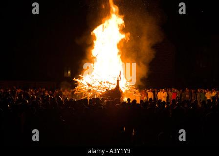 dh Up Helly Aa fire procession LERWICK SHETLAND Guizers watching Viking longship galley Moogi alight at burning - Stock Photo