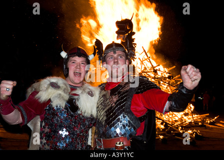 dh Up Helly Aa fire procession LERWICK SHETLAND Two Vikings with longship galley alight viking warriors costume - Stock Photo