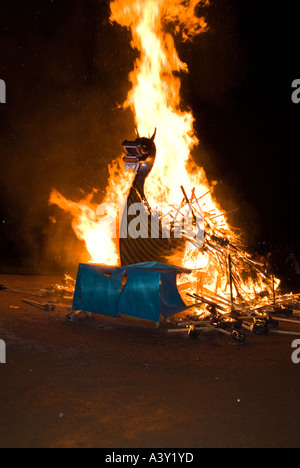 dh Up Helly Aa fire procession LERWICK SHETLAND Viking longship galley Moogi alight at burning site festival - Stock Photo