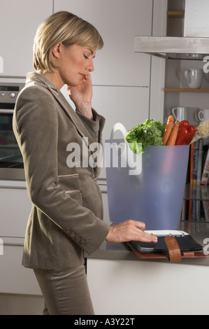 portrait of young businesswoman standing in kitchen talking on mobile phone and looking at her diary - Stock Photo