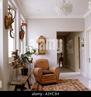 Leather armchair in hallway on patterned rug - Stock Photo