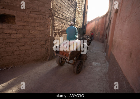 A man on a horse drawn cart is delivering goods in the backstreets of Marrakech - Stock Photo