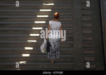 woman climbing a staircase from an underpass towards the light - Stock Photo