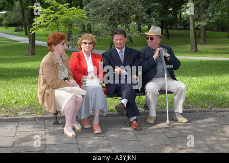 Four mature friends stting on a park bench on a public holiday - Stock Photo