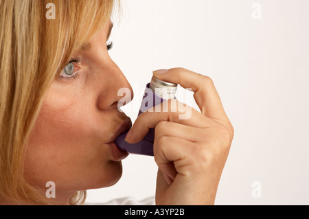 ATTRACTIVE HEALTHY YOUNG WOMAN USING ASTHMA INHALER - Stock Photo