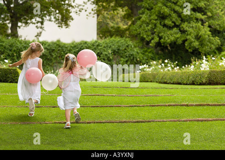 Two young girls running in garden, holding balloons, back view - Stock Photo