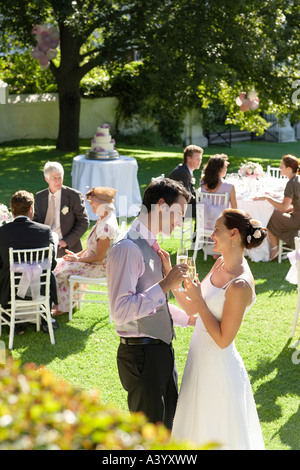 Mid adult bride and groom in garden, toasting among wedding guests - Stock Photo