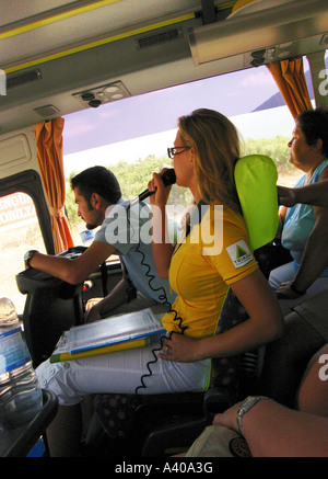Women guide taking to tourists on bus Turkey - Stock Photo