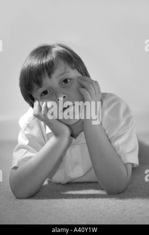 A black white image of a boy with his head in his hands looking forwards - Stock Photo