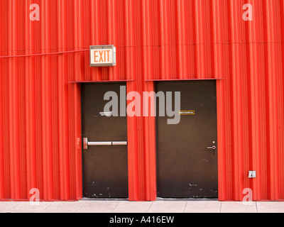 Two brown metal doors in a corrugated metal building with exit sign - Stock Photo