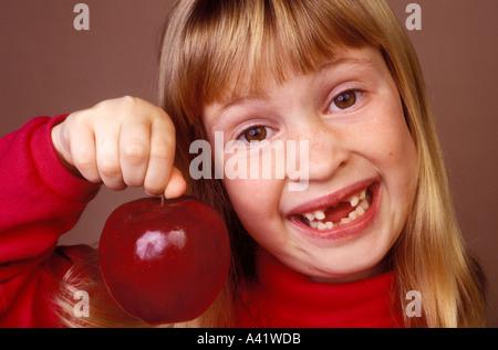 Little girl holding apple missing front teeth - Stock Photo