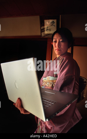 Japanese woman wearing a colourful silk kimono and holding a powerful laptop computer Nara prefecture Japan - Stock Photo