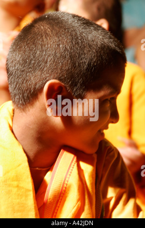 Kid monk during Aarti rituals at the banks of Ganga in Rishikesh, Uttranchal India - Stock Photo