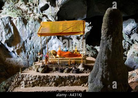 Reclining Bronze Buddha inside Phu Kham Cave Vang Vieng Laos - Stock Photo