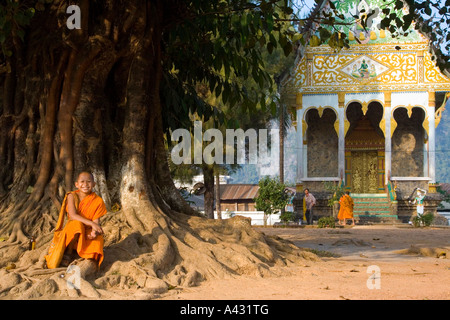 Novice Monk in front of a Tree and Wat Kang Temple Vang Vieng Laos - Stock Photo