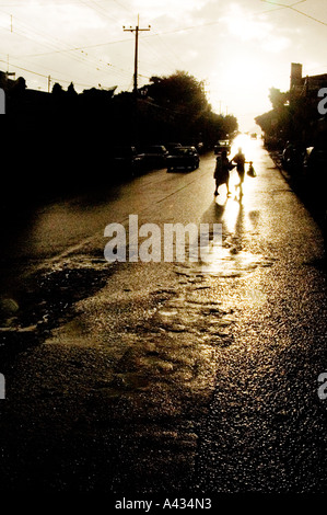 2 pedestrians silhouettes cross rain slicked highway in village near Lake Chapala in state of Jalisco Mexico - Stock Photo
