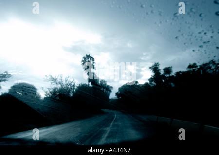 rain slicked rural highway taken through windshield near Lake Chapala in Mexico - Stock Photo