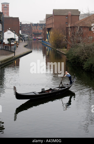 A Gondola traveling along the canal network in the centre of Birmingham West Midlands England - Stock Photo