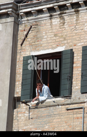 Venice Italy Venetian resident at the upper window of his town house in the Rialto San Polo area - Stock Photo
