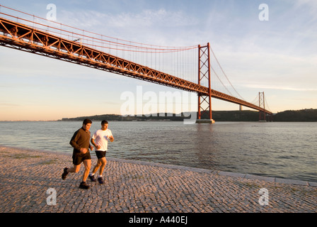 Joggers running alongside the river RIO TEJO under the PONT 25 DE ABRIL bridge in the Alcantara district of Lisbon - Stock Photo