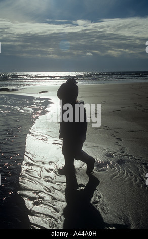 Child at play on a Cornish beach. Gunwalloe Dollar Cove, The Lizard Cornwall Uk - Stock Photo