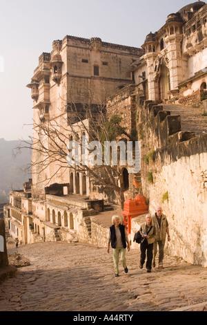 India Rajasthan Bundi Garh Palace western tourists walking up the steep path towards entrance - Stock Photo