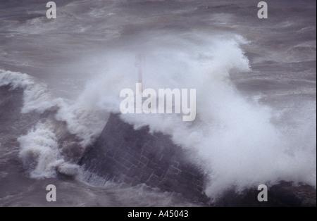 Storm waves crash over a breakwater at Dawlish Devon UK - Stock Photo