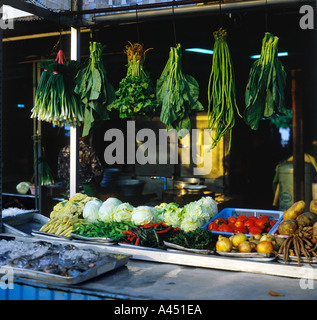 Thai green vegetables suspended over counter level display of fresh vegetables plus fish in ice on outdoor cart in Hua Hin Thailand