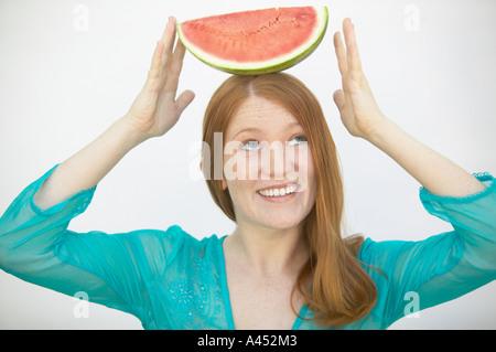 Woman balancing watermelon on her head - Stock Photo