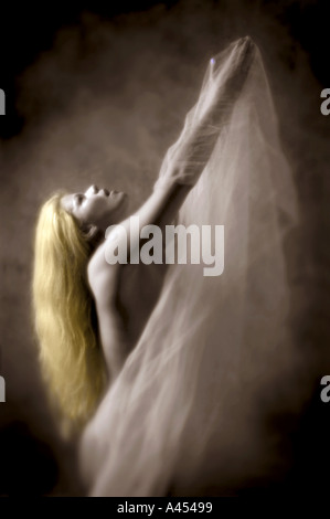 A vertical image of a woman with blonde hair reaching upwards with both arms while holding a fine fabric with her - Stock Photo