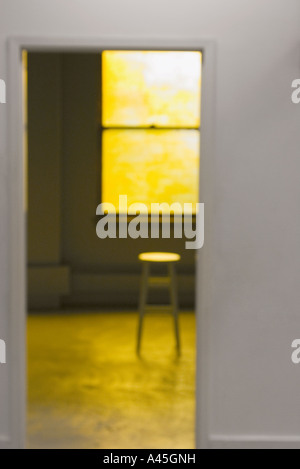 selective focus of small room with wooden stool set in warm yellow light - Stock Photo