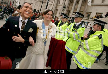 demonstrators dressed as queen elizabeth and u s president george w bush walk past british police officers in trafalgar - Stock Photo