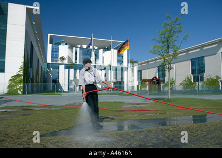 Man watering the lawn in front of the Federal Chancellery Building in Berlin, Germany - Stock Photo