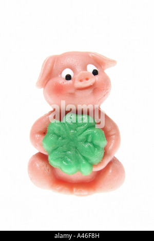 Marzipan pig with a four-leaf clover on white background - Stock Photo