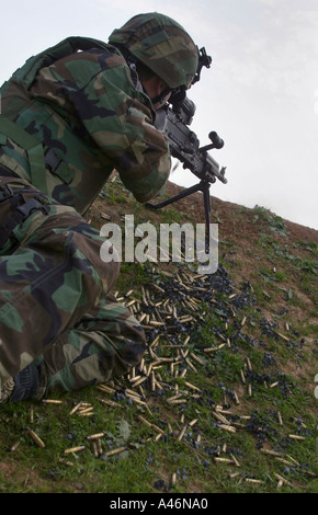 Machine gun bullet casings lie next to a US Special Forces soldier firing on the Iraqi Army during a battle in Kurdistan, - Stock Photo