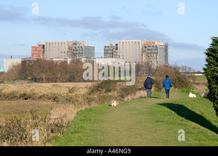 Bradwell Waterside on River Blackwater people walking on footpath on sea wall with Bradwell nuclear power station - Stock Photo