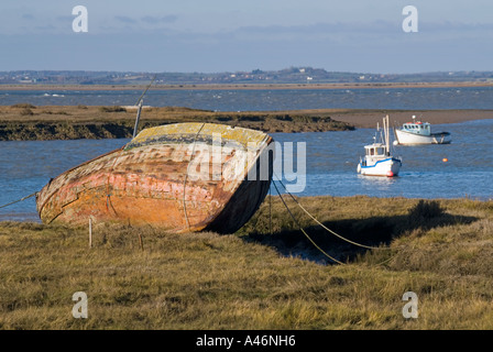 Bradwell Waterside on River Blackwater abandoned boat hull with boats at moorings Essex England UK - Stock Photo