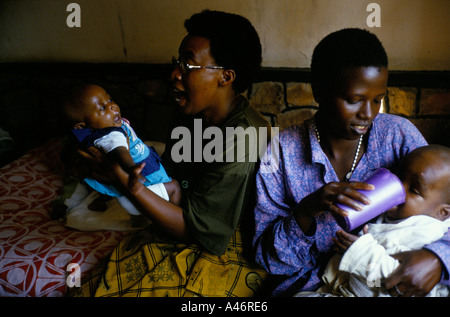 maggy and another carer feed two aids orphans who are resident at shalom house ruyigi burundi - Stock Photo