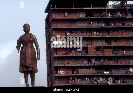 A run down block of flats stands behind a statue of queen nzinga in kinixixi square a warrior queen who opposed - Stock Photo