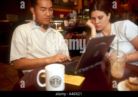 John and Shane Vu from America surf the internet with a laptop at a Starbucks cafe on Old Broad Street in the City - Stock Photo